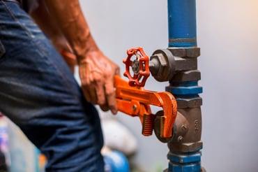 bigstock-Plumber-Using-A-Wrench-To-Repa-354004223